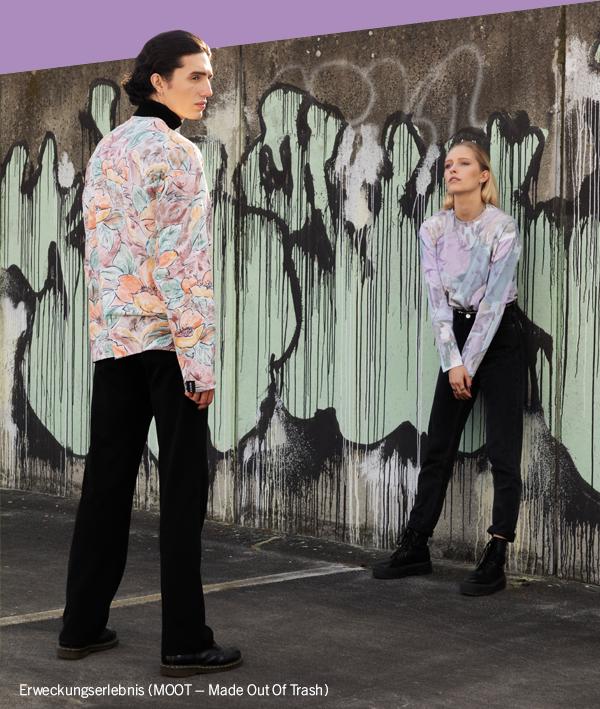 Urbane Szene: Frau lehnt an Wand mit Graffiti, im Vordergrund steht ein Mann. Beide tragen gemusterte Oberteile der Marke Moot.